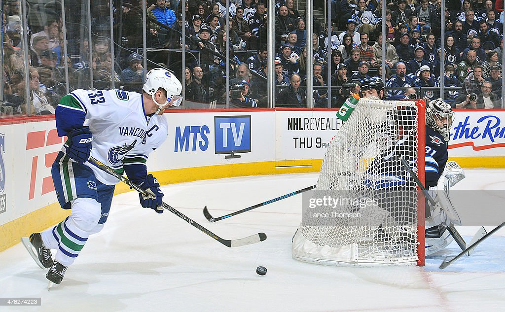 Goaltender Ondrej Pavelec #31 of the Winnipeg Jets keeps an eye on <a gi-track='captionPersonalityLinkClicked' href=/galleries/search?phrase=Henrik+Sedin&family=editorial&specificpeople=202574 ng-click='$event.stopPropagation()'>Henrik Sedin</a> #33 of the Vancouver Canucks as he plays the puck behind the net during third period action at the MTS Centre on March 12, 2014 in Winnipeg, Manitoba, Canada.