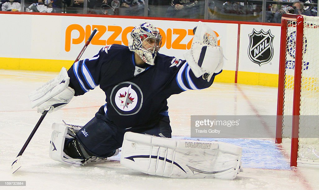 Goaltender <a gi-track='captionPersonalityLinkClicked' href=/galleries/search?phrase=Ondrej+Pavelec&family=editorial&specificpeople=3644118 ng-click='$event.stopPropagation()'>Ondrej Pavelec</a> #31 of the Winnipeg Jets keeps an eye on the puck as he makes a third period glove save against the Ottawa Senators at the MTS Centre on January 19, 2013 in Winnipeg, Manitoba, Canada.