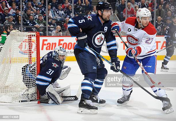 Goaltender Ondrej Pavelec of the Winnipeg Jets looks through a screen set by teammate Mark Stuart and Alex Galchenyuk of the Montreal Canadiens...