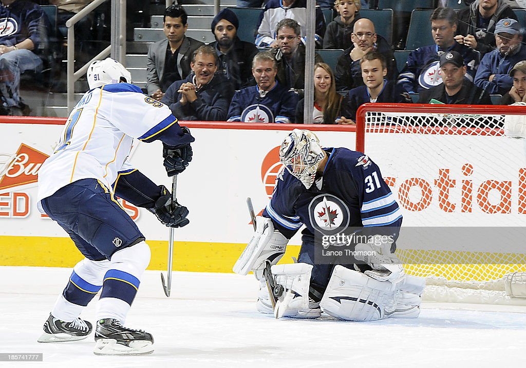 Goaltender Ondrej Pavelec #31 of the Winnipeg Jets makes a pad save on <a gi-track='captionPersonalityLinkClicked' href=/galleries/search?phrase=Vladimir+Tarasenko&family=editorial&specificpeople=6142635 ng-click='$event.stopPropagation()'>Vladimir Tarasenko</a> #91 of the St. Louis Blues during the shootout at the MTS Centre on October 18, 2013 in Winnipeg, Manitoba, Canada. The Jets defeated the Blues 4-3.