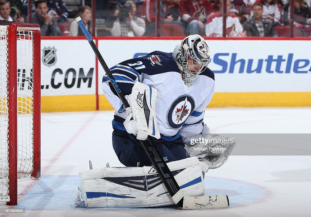 Goaltender Ondrej Pavelec #31 of the Winnipeg Jets makes a pad save on the shot from the Phoenix Coyotes during the first period of the NHL game at Jobing.com Arena on April 1, 2014 in Glendale, Arizona. The Jets defeated the Coyotes 2-1 in an overtime shootout.