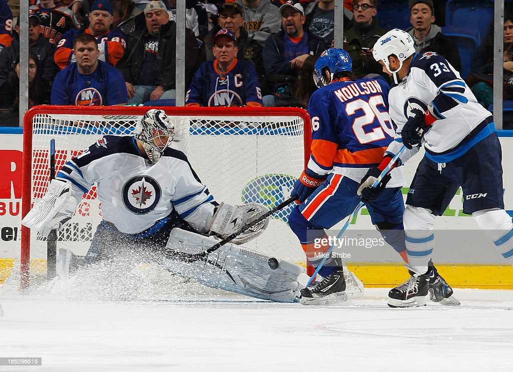 Goaltender Ondrej Pavelec #31 of the Winnipeg Jets makes a save as teammate Dustin Byfuglien #33 and Matt Moulson #26 of the New York Islanders look for the rebound at Nassau Veterans Memorial Coliseum on April 2, 2013 in Uniondale, New York.