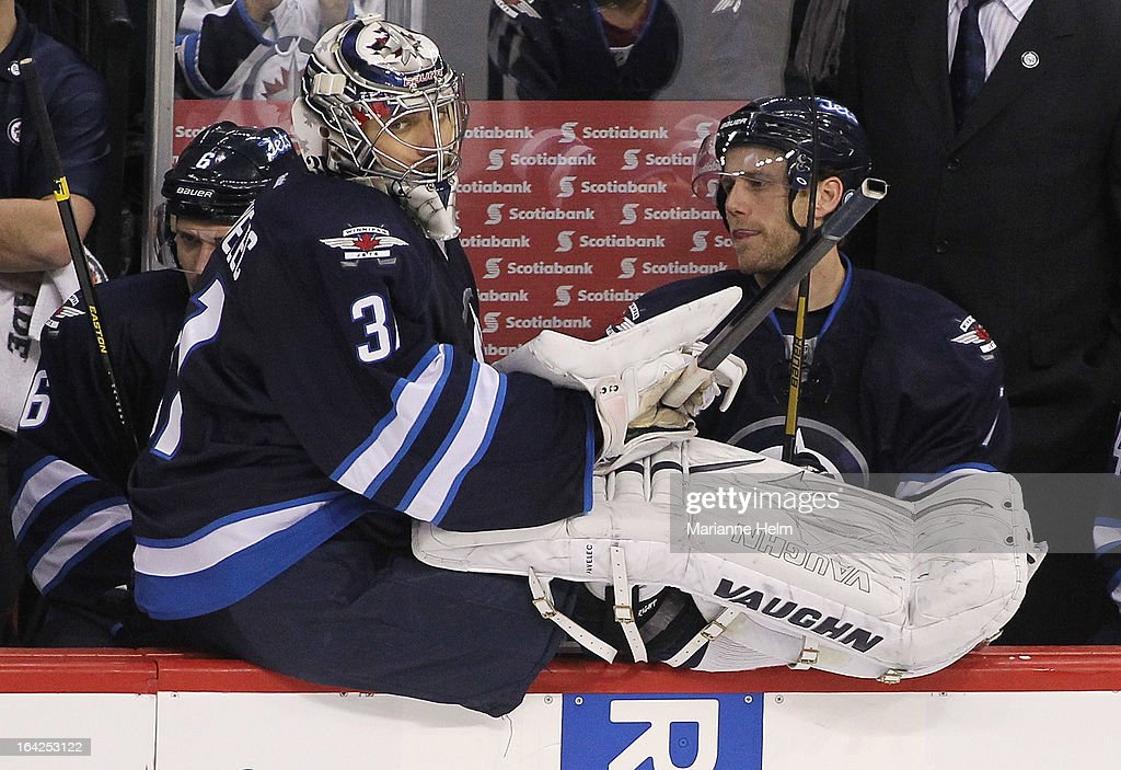 Goaltender Ondrej Pavelec #31 of the Winnipeg Jets sits on the boards in front of <a gi-track='captionPersonalityLinkClicked' href=/galleries/search?phrase=Derek+Meech&family=editorial&specificpeople=2234391 ng-click='$event.stopPropagation()'>Derek Meech</a> #7 after getting pulled in attempt to give the Jets an advantage during third-period action against the Washington Capitals on March 21, 2013 at the MTS Centre in Winnipeg, Manitoba, Canada.