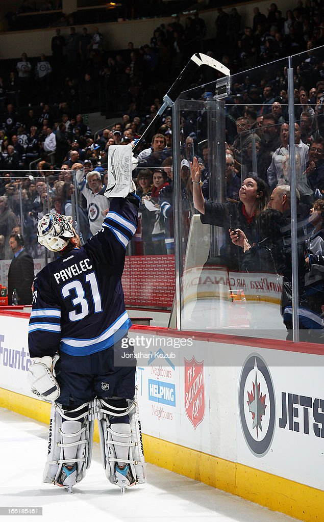 Goaltender Ondrej Pavelec #31 of the Winnipeg Jets throws his stick over the glass to fans following a 4-1 victory over the Buffalo Sabres at the MTS Centre on April 9, 2013 in Winnipeg, Manitoba, Canada.