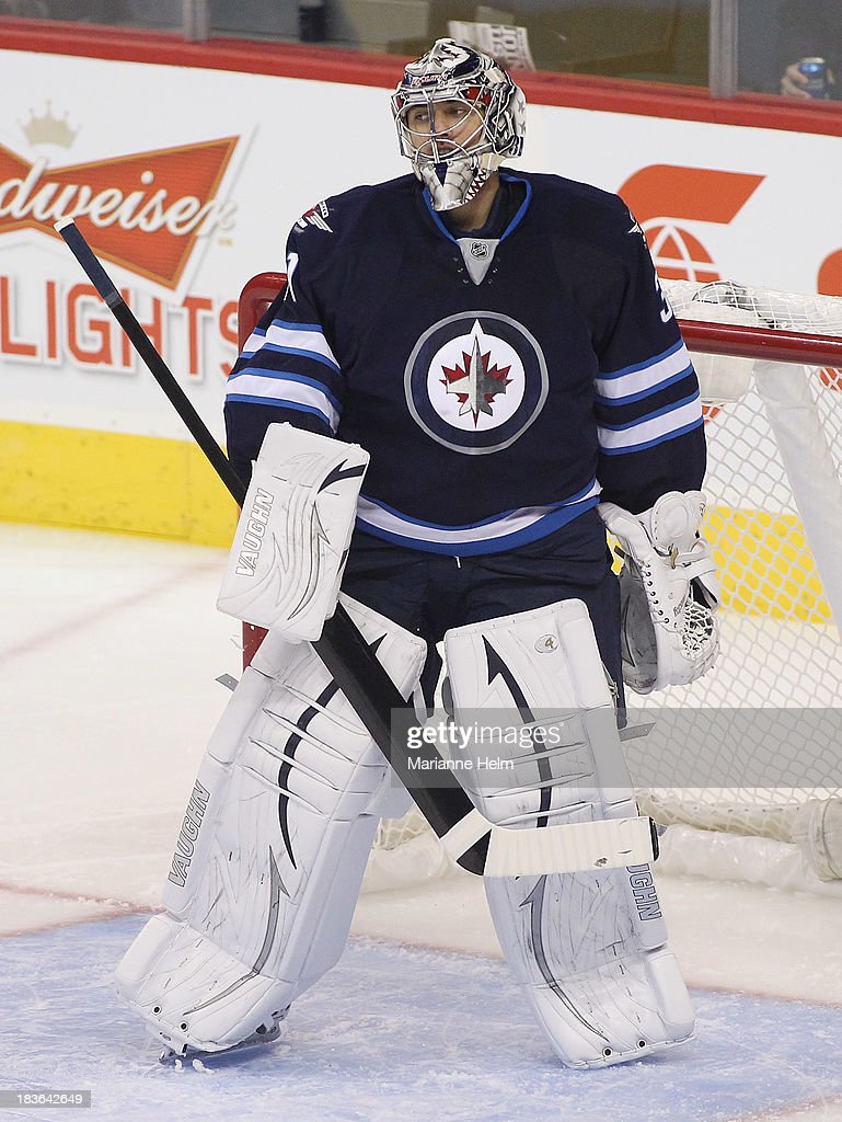 Goaltender Ondrej Pavelev #31 of the Winnipeg Jets looks around during a break in play in first period action during an NHL preseason game against the Boston Bruins at the MTS Centre on September 26, 2013 in Winnipeg, Manitoba, Canada.