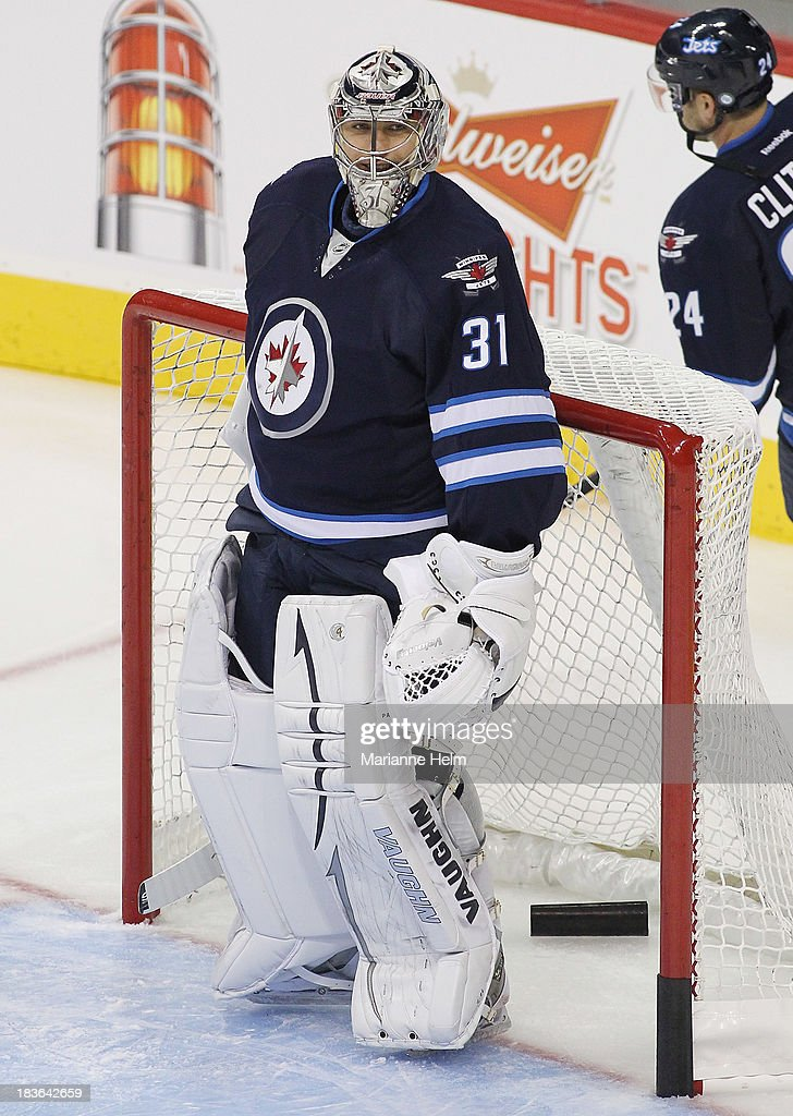 Goaltender Ondrej Pavelev #31 of the Winnipeg Jets smiles during warmup before an NHL preseason game against the Boston Bruins at the MTS Centre on September 26, 2013 in Winnipeg, Manitoba, Canada.