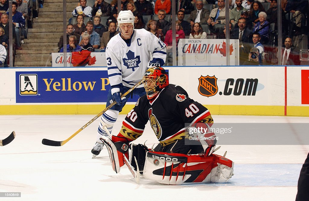 Goaltender Patrick Lalime #40 of the Ottawa Senators goes down to stop the puck as center Mats Sundin #13 of the Toronto Maple Leafs looks on at Air Canada Centre in Toronto, Ontario, Canada on October 12, 2002.