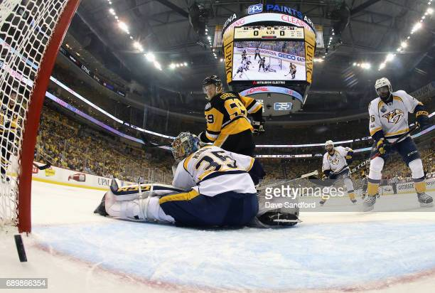 Goaltender Pekka Rinne of the Nashville Predators and Jake Guentzel of the Pittsburgh Penguins watch the puck go in on a shot by Evgeni Malkin during...
