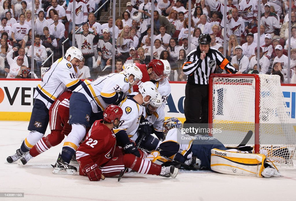 Goaltender Pekka Rinne of the Nashville Predators covers the puck as Daymond Langkow and Gilbert Brule of the Phoenix Coyotes crash the net in Game...