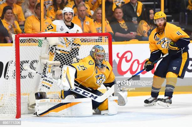 Goaltender Pekka Rinne of the Nashville Predators defends his net as teammate Ryan Ellis and Sidney Crosby of the Pittsburgh Penguins look on in the...