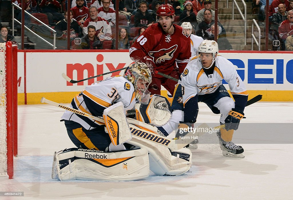Goaltender Pekka Rinne #35 of the Nashville Predators makes a blocker save as Seth Jones #3 of the Predators and Jordan Martinook #48 of the Arizona Coyotes skate in during the second period at Gila River Arena on December 11, 2014 in Glendale, Arizona.