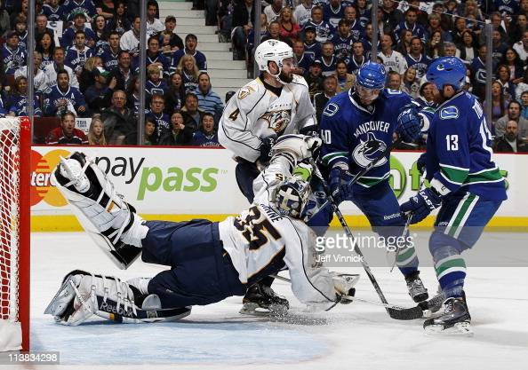 Goaltender Pekka Rinne of the Nashville Predators makes a save in front of teammate Cody Franson while Raffi Torres Maxim Lapierre of the Vancouver...