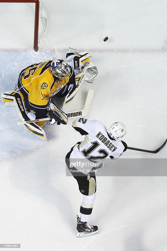 Goaltender Pekka Rinne of the Nashville Predators protects the net as Chuck Kobasew of the Pittsburgh Penguins shoots the puck at Bridgestone Arena...