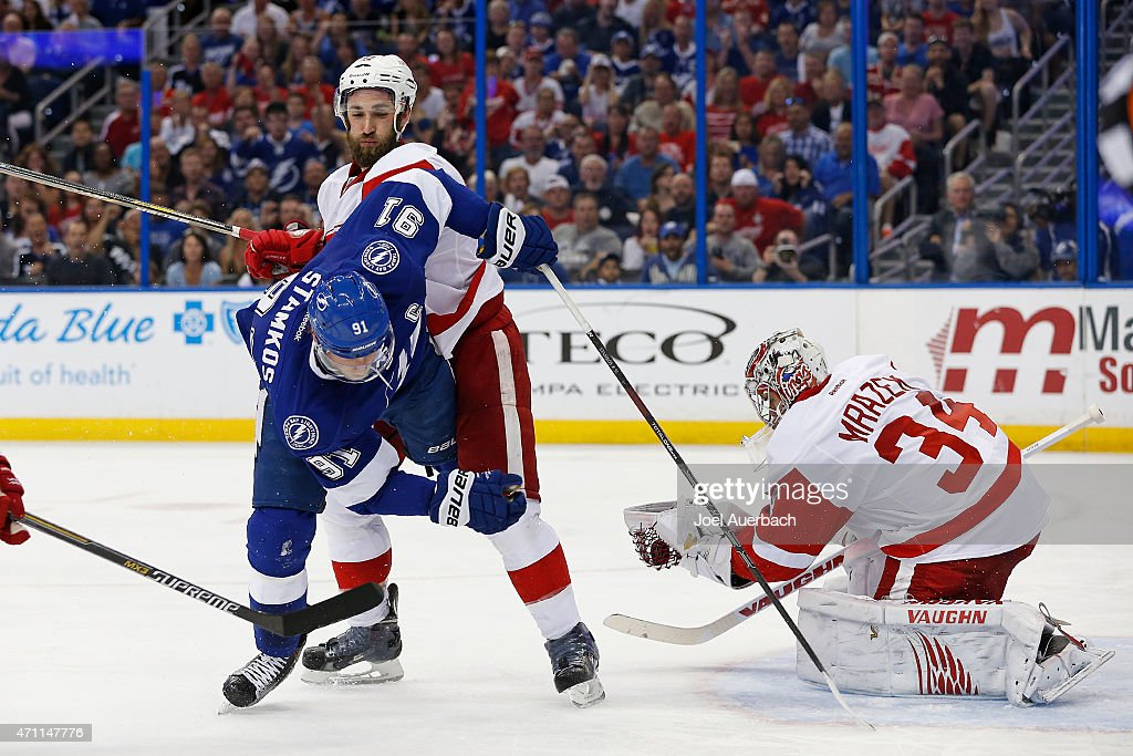 Goaltender Petr Mrazek catches the puck as Kyle Quincey of the Detroit Red Wings upends Steven Stamkos of the Tampa Bay Lightning during the second...