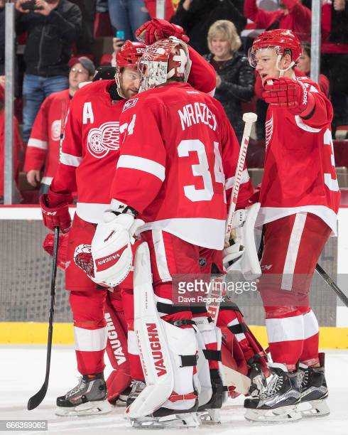 Goaltender Petr Mrazek of the Detroit Red Wings is congratulated by teammates Niklas Kronwall and Evgeny Svechnikov following a shootout win of an...