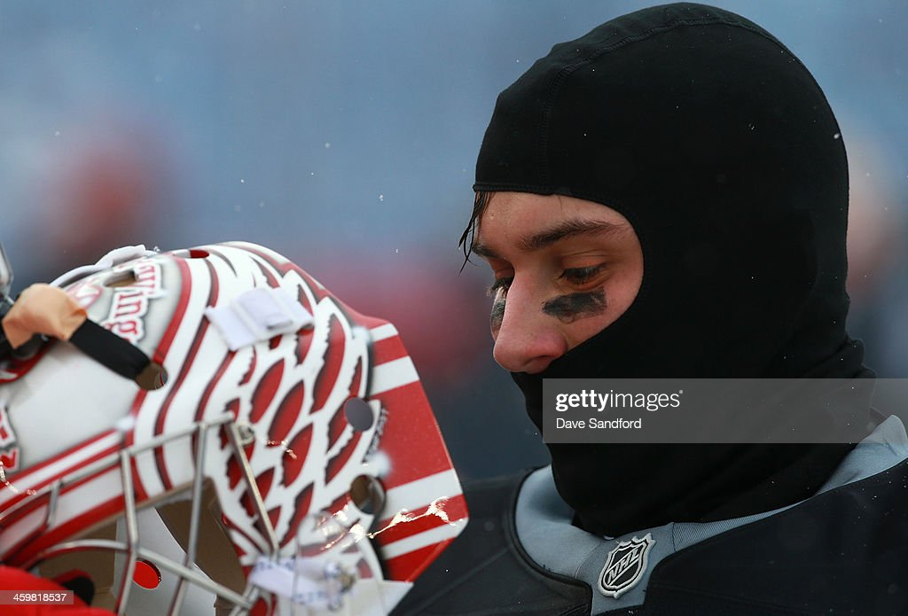 Goaltender <a gi-track='captionPersonalityLinkClicked' href=/galleries/search?phrase=Petr+Mrazek&family=editorial&specificpeople=6514148 ng-click='$event.stopPropagation()'>Petr Mrazek</a> #34 of the Detroit Red Wings puts on his mask during the 2014 Bridgestone NHL Winter Classic team practice session on December 31, 2013 at Michigan Stadium in Ann Arbor, Michigan.