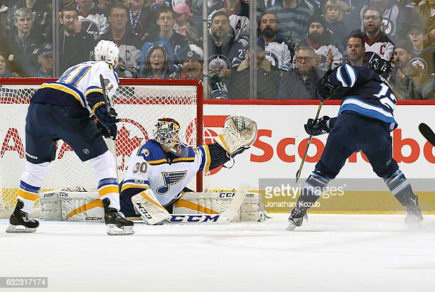 Goaltender Pheonix Copley of the St Louis Blues does the splits in the crease as Drew Stafford of the Winnipeg Jets shoots the puck high over the...