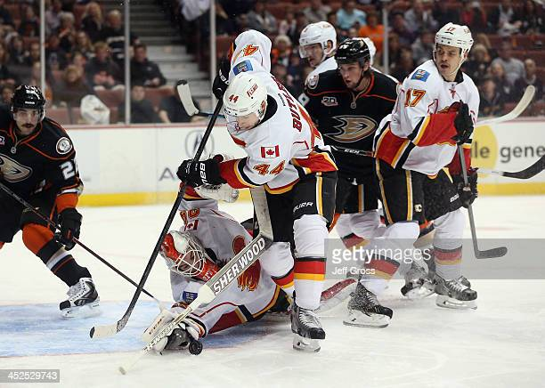 Goaltender Reto Berra of the Calgary Flames loses his stick trying to make a save as teammate Chris Butler scrambles to clear the puck against the...