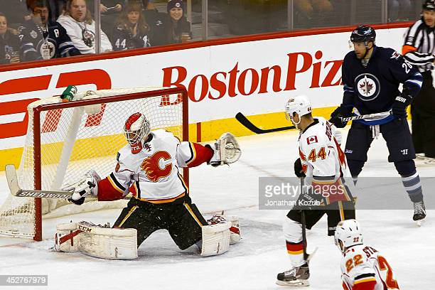 Goaltender Reto Berra of the Calgary Flames reacts as the puck flies towards the net as teammate Chris Butler and Blake Wheeler of the Winnipeg Jets...