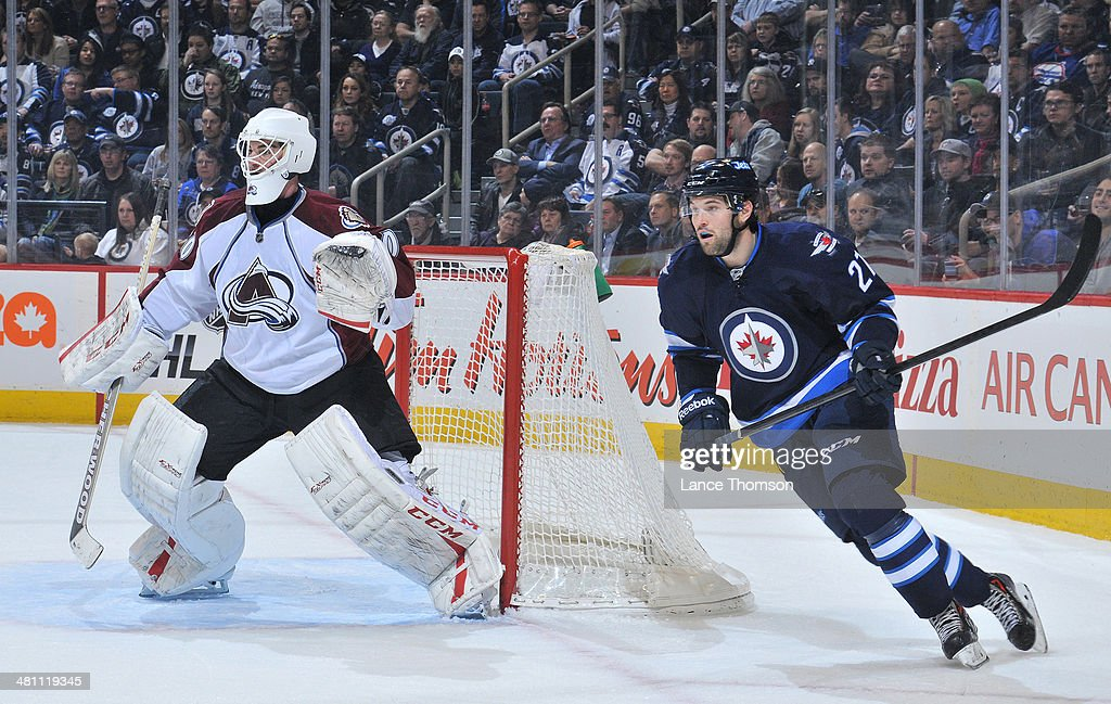 Goaltender Reto Berra #20 of the Colorado Avalanche and Eric Tangradi #27 of the Winnipeg Jets keep an eye on the play during first period action at the MTS Centre on March 19, 2014 in Winnipeg, Manitoba, Canada. The Jets defeated the Avs 5-4 in overtime.