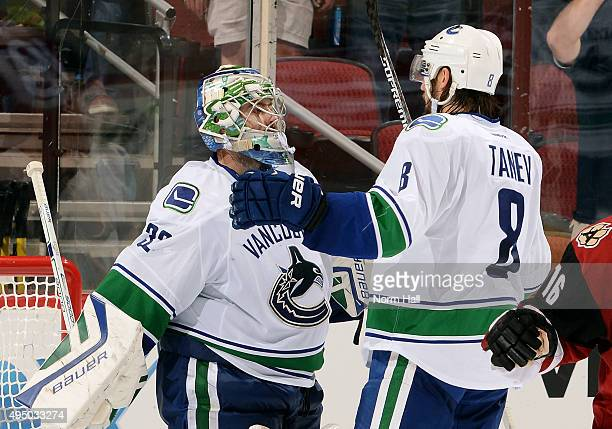 Goaltender Richard Bachman and Christopher Tanev of the Vancouver Canucks celebrate a 43 victory against the Arizona Coyotes at Gila River Arena on...