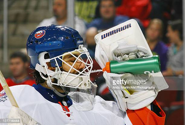 Goaltender Rick DiPietro of the New York Islanders cools down with a drink during a timeout against the New Jersey Devils during the preseason game...