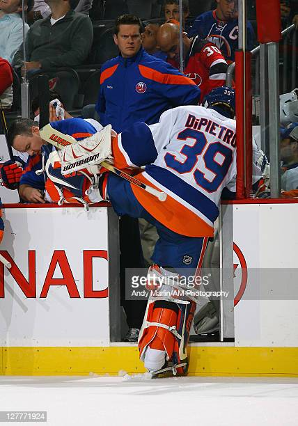 Goaltender Rick DiPietro of the New York Islanders has his skate worked on during a timeout against the New Jersey Devils during the preseason game...