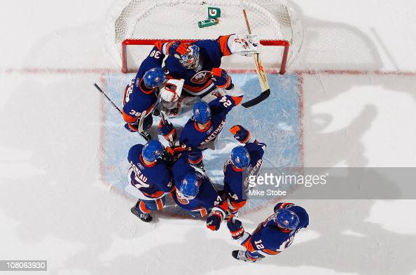 Goaltender Rick DiPietro of the New York Islanders is mobbed by his teammates after defeating the Buffalo Sabres on January 15 2011 at Nassau...