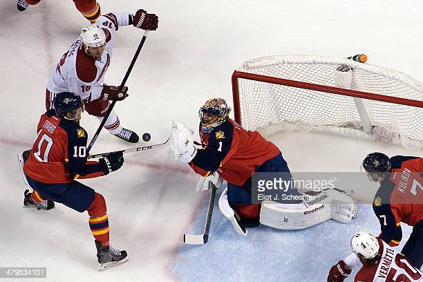 Goaltender Roberto Luongo of the Florida Panthers and teammate Joey Crabb defend the net against David Moss of the Phoenix Coyotes at the BBT Center...