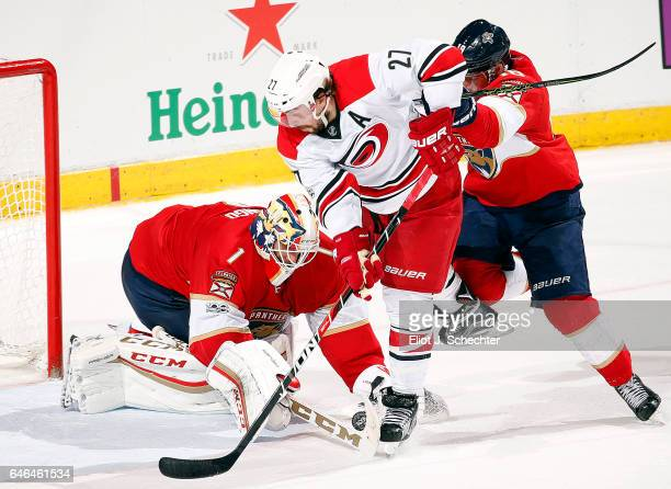 Goaltender Roberto Luongo of the Florida Panthers defends the net in overtime with the help of teammate Reilly Smith against Justin Faulk of the...