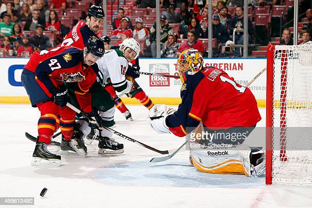 Goaltender Roberto Luongo of the Florida Panthers defends the net with the help of teammate Colby Robak against Jason Zucker of the Minnesota Wild at...