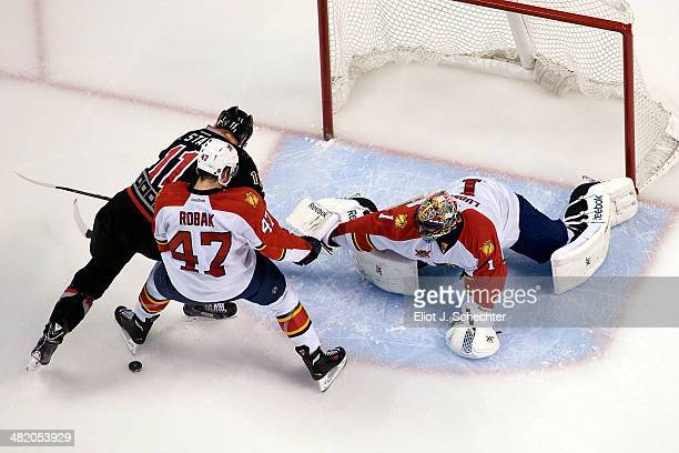 Goaltender Roberto Luongo of the Florida Panthers defends the net with the help of teammate Colby Robak against Jordan Staal of the Carolina...