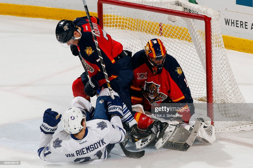 Goaltender <a gi-track='captionPersonalityLinkClicked' href=/galleries/search?phrase=Roberto+Luongo&family=editorial&specificpeople=202638 ng-click='$event.stopPropagation()'>Roberto Luongo</a> #1 of the Florida Panthers defends the net with the help of teammate Dmitry Kulikov #7 against James van Riemsdyk #21 of the Toronto Maple Leafs at the BB&T Center on April 10, 2014 in Sunrise, Florida.