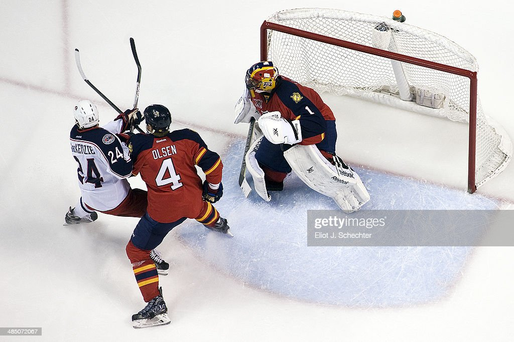 Goaltender Roberto Luongo #1 of the Florida Panthers defends the net with the help of teammate Dylan Olsen #4 against Derek MacKenzie #24 of the Columbus Blue Jackets at the BB&T Center on April 12, 2014 in Sunrise, Florida.