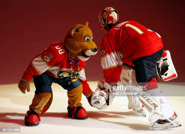 Goaltender Roberto Luongo of the Florida Panthers low fives team Mascot Stanley C Panther after their shootout win against the Carolina Hurricanes at...