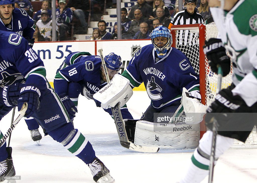 Goaltender Roberto Luongo #1 of the Vancouver Canucks and Ryan Stanton #18 of the Vancouver Canucks watch the puck against the Dallas Stars during the third period of their NHL game at Rogers Arena on November 17, 2013 in Vancouver, British Columbia, Canada.