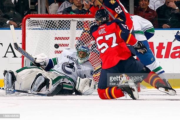 Goaltender Roberto Luongo of the Vancouver Canucks defends the net against Marcel Goc of the Florida Panthers at the BankAtlantic Center on January 9...