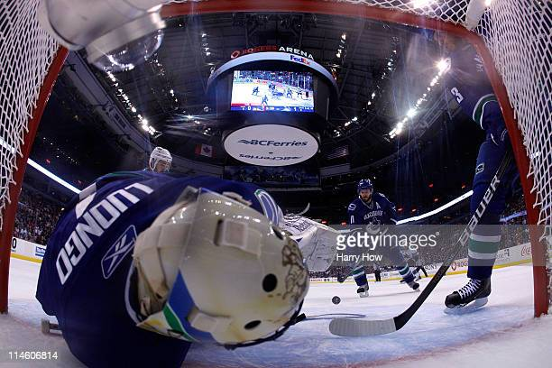 Goaltender Roberto Luongo of the Vancouver Canucks makes a save against the San Jose Sharks as teammate Ryan Kesler looks to clear the puck from the...