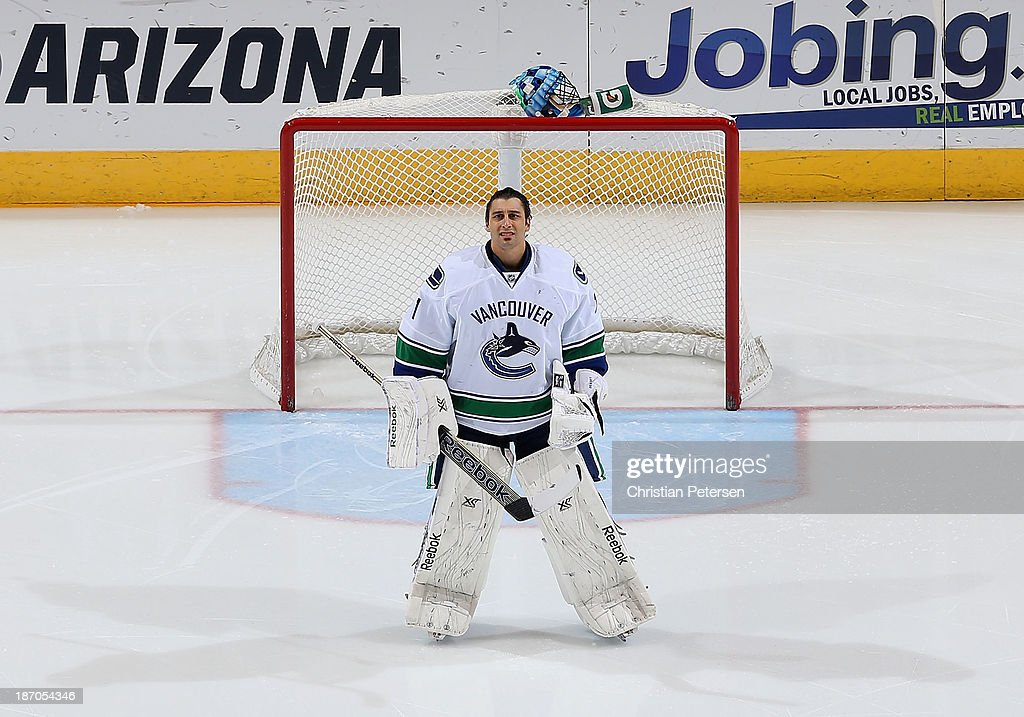 Goaltender <a gi-track='captionPersonalityLinkClicked' href=/galleries/search?phrase=Roberto+Luongo&family=editorial&specificpeople=202638 ng-click='$event.stopPropagation()'>Roberto Luongo</a> #1 of the Vancouver Canucks stands attended for the National Anthem before the NHL game against the Phoenix Coyotes at Jobing.com Arena on November 5, 2013 in Glendale, Arizona. The Coyotes defeated the Canucks 3-2 in an overtime shoot out.