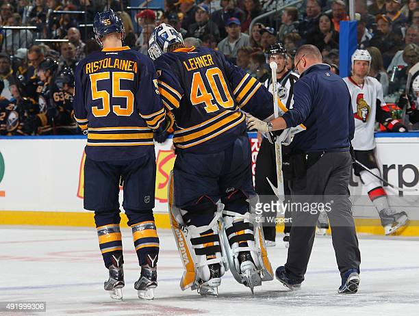 Goaltender Robin Lehner of the Buffalo Sabres is helped off the ice by Rasmus Ristolainen and athletic trainer Tim Macre after an injury in a game...
