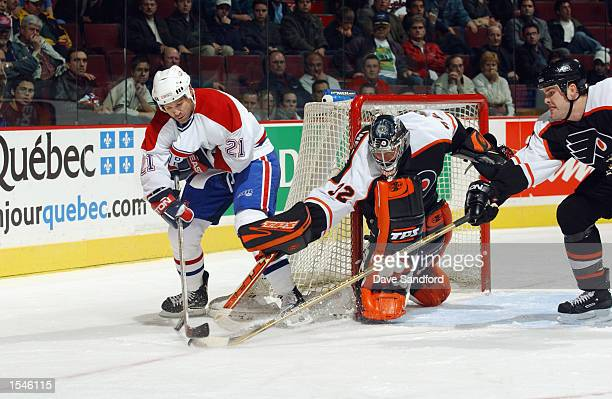 Goaltender Roman Cechmanek of the Philadelphia Flyers gets help from teammate Chris Therien as he pokes the puck away from right wing Randy McKay of...