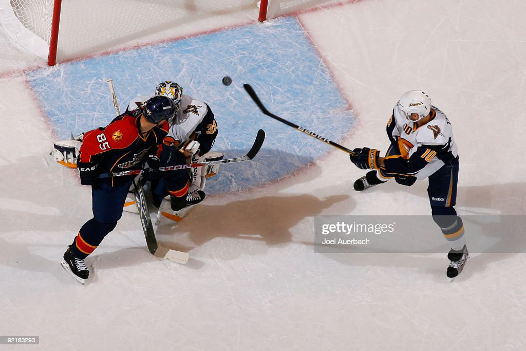 Goaltender Ryan Miller makes a save and Henrik Tallinder of the Buffalo Sabres clears the puck on a shot taken by Rostislav Olesz of the Florida...