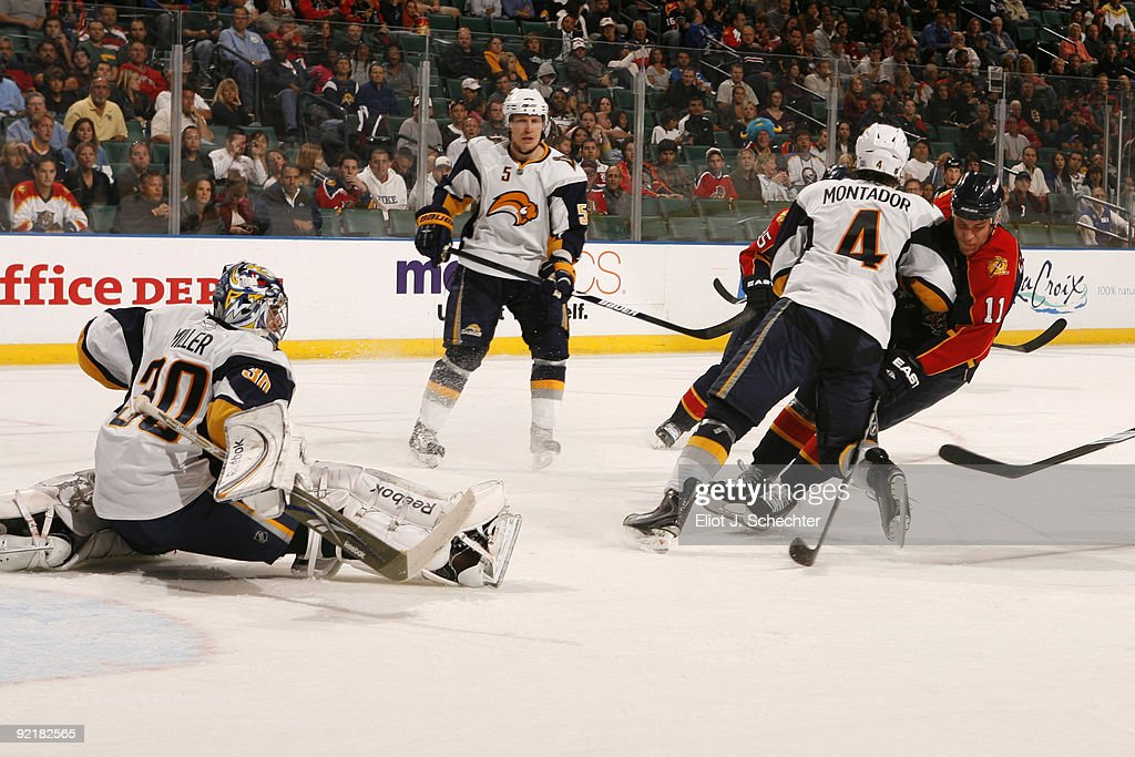 Goaltender Ryan Miller of the Buffalo Sabres defends the net with teammate Steve Montador against Gregory Campbell of the Florida Panthers at the...