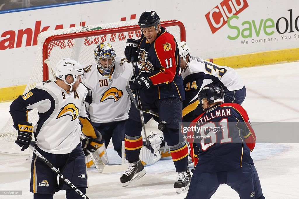 Goaltender Ryan Miller of the Buffalo Sabres drops down to his pads as Gregory Campbell is hit with the puck on a shot taken by Cory Stillman of the...