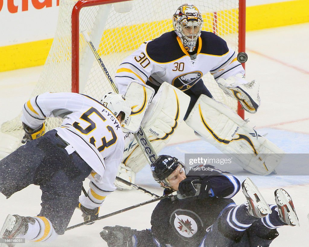 Goaltender Ryan Miller #30 of the Buffalo Sabres keeps an eye on the puck as teammate Mark Pysyk #53 and Bryan Little #18 of the Winnipeg Jets fall in front of the net during third period action at the MTS Centre on April 9, 2013 in Winnipeg, Manitoba, Canada. The Jets defeated the Sabres 4-1.