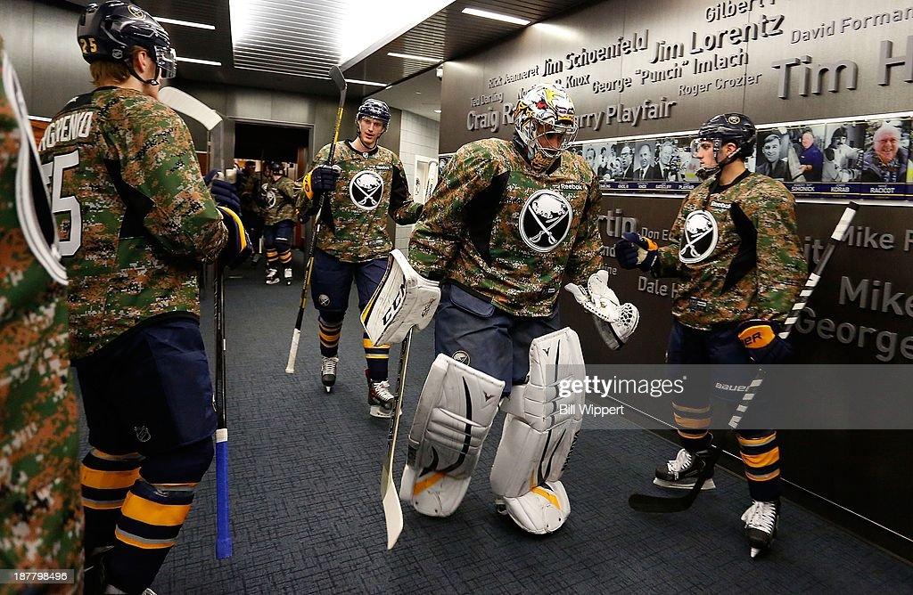 Goaltender Ryan Miller #30 of the Buffalo Sabres leads his team onto the ice wearing camouflage jerseys to warm up for their game against the Los Angeles Kings on November 12, 2013 at the First Niagara Center in Buffalo, New York.