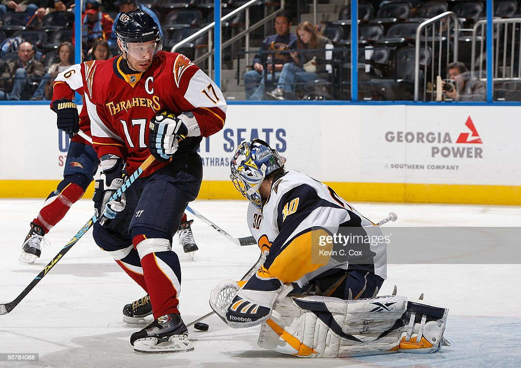 Goaltender Ryan Miller of the Buffalo Sabres saves a shot on goal in front of Ilya Kovalchuk of the Atlanta Thrashers at Philips Arena on January 14...