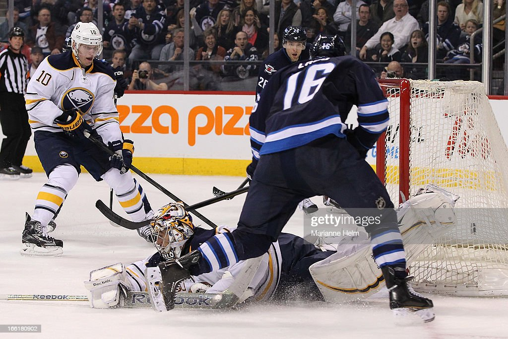 Goaltender Ryan Miller #30 of the Buffalo Sabres sprawls on the ice as Andrew Ladd #16 of the Winnipeg Jets shoots for a goal during second-period action on April 9, 2013 at the MTS Centre in Winnipeg, Manitoba, Canada.