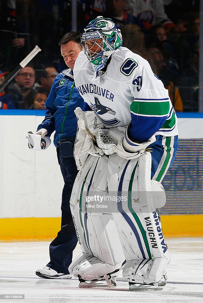 Goaltender Ryan Miller of the Vancouver Canucks is helped off the ice after being injured during the game against the New York Islanders at Nassau...
