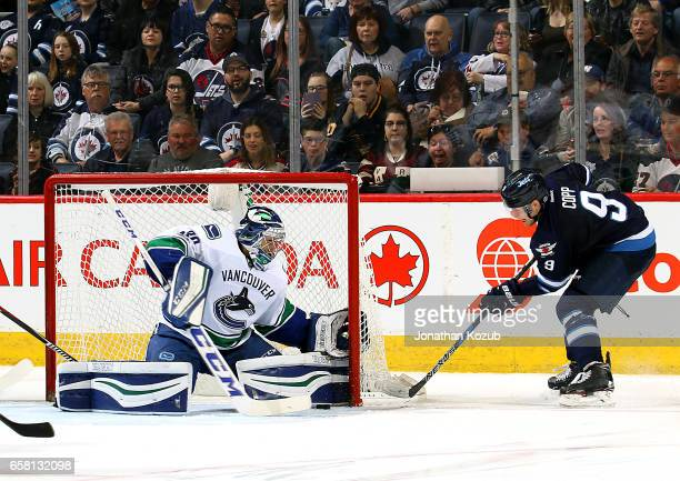 Goaltender Ryan Miller of the Vancouver Canucks stops the puck on the goal line as Andrew Copp of the Winnipeg Jets looks on during third period...